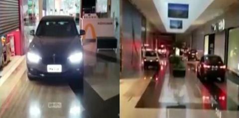 Carros circulam dentro de shopping para realizar compras